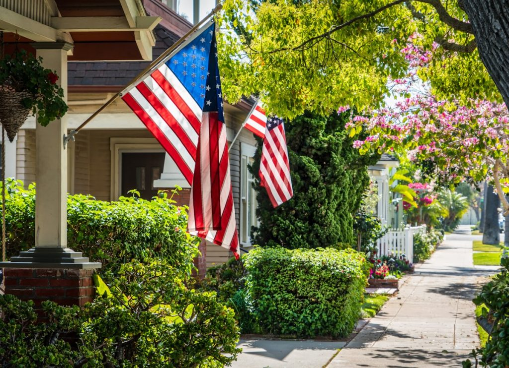 american flags on homes along sidewalk